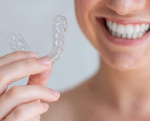 Eine Frau hält eine unsichtbare Zahnspange in den Händen
