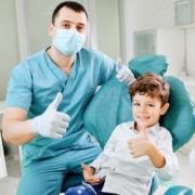 Kind und Kieferorthopäde zeigen mit dem Daumen nach oben und lächeln