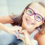 Kleines Kind mit Brille laechelt mit einer festen Zahnspange