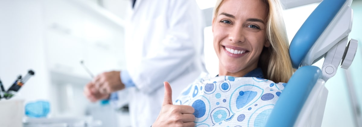 Frau laechelt nach einer erfolgreichen Behandlung ihrer Zahnfehlstellung