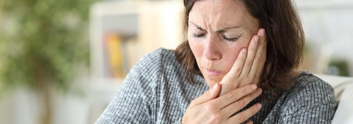 aeltere frau haelt sich die haende an die wange aufgrund von Zahnspangen schmerzen