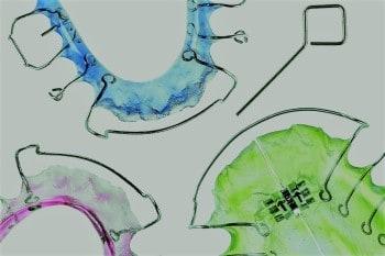 Beispiel Kieferorthopädie: drei herausnehmbare Zahnspangen in verschiedenen Farben