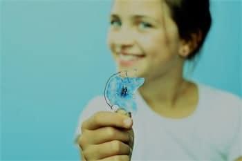 Beispiel Kieferorthopädie: lächelndes Kind hält einen herausnehmbaren Lückenhalter
