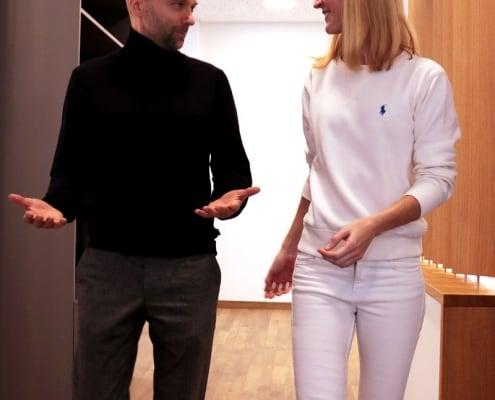 Dr. Eva Huff empfängt einen erwachsenen Patient im Empfangsbereich der Praxis DENTAL ONE | Kieferorthopäde München Schwabing - Münchner Freiheit, beide befinden sich im Gespräch und sind auf dem Weg in ein Behandlungszimmer