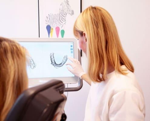 Dr. Eva Huff erklärt einer erwachsenen Patientin die kieferorthopädische Behandlung anhand einer Simulation des Behandlungsergebnisses in einem Behandlungszimmer der Praxis DENTAL ONE | Kieferorthopäde München Schwabing - Münchner Freiheit, im Hintergrund ist ein Bild zu sehen