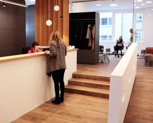 Empfang der Praxis DENTAL ONE | Kieferorthopäde München Schwabing - Münchner Freiheit | Dr. Eva Huff mit Patientin und Helferin, im Hintergrund ist das Wartezimmer mit Patienten zu sehen