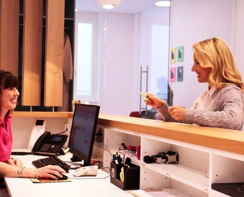eine erwachsene Patientin meldet sich bei einer Helferin am Empfang der Praxis DENTAL ONE | Kieferorthopäde München Schwabing - Münchner Freiheit | Dr. Eva Huff an, beide lächeln sich freundlich an