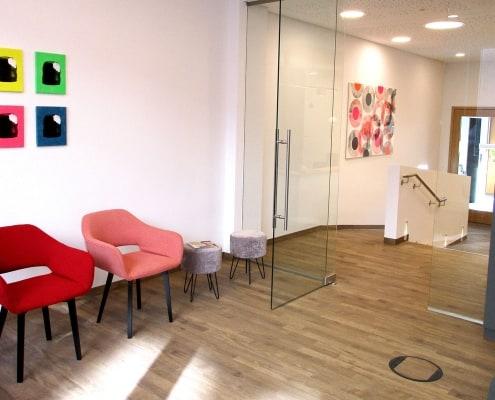 Wartezimmer der Praxis DENTAL ONE | Kieferorthopäde München Schwabing - Münchner Freiheit | Dr. Eva Huff mit Blick zum Empfang und zur Eingangstür