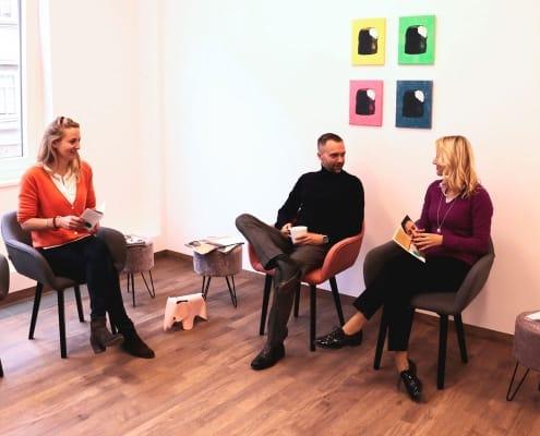 drei erwachsene Patienten sitzen im Wartezimmer der Praxis DENTAL ONE | Kieferorthopäde München Schwabing - Münchner Freiheit | Dr. Eva Huff und unterhalten sich