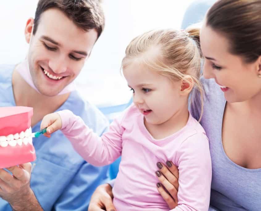 Einem kleinen Mädchen wird zu Beginn der Behandlung das richtige Zähneputzen gezeigt