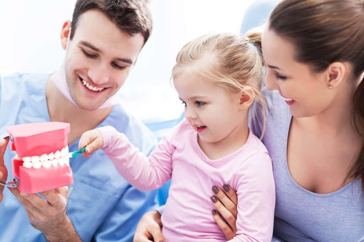 ein Kieferorthopäde übt mit einem Kind das Zähneputzen, die Mutter hat das Kind auf dem Schoß