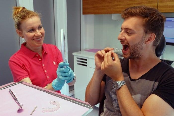 beim Behandlungsbeginn setzt der Patient seine erste Invisalign-Zahnschiene ein, die Kieferorthopädin unterstützt den Patienten dabei
