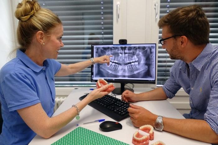 Kieferorthopädin und Patient bei der Planbesprechung, Kieferorthopädin erläutert Röntgenbild