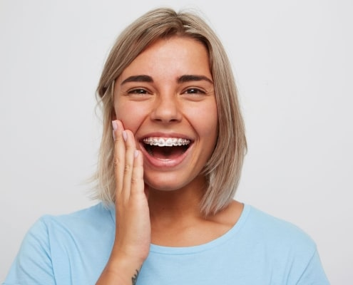 erwachsene blonde Frau mit fester Zahnspange und rosa-farbigen Gummis
