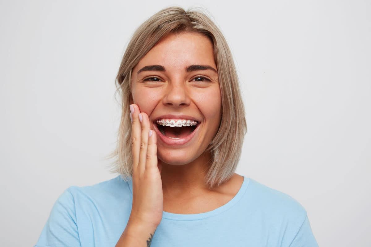 erwachsene Frau lächelt mit Zahnspange mit Metallbrackets und pinken Gummis
