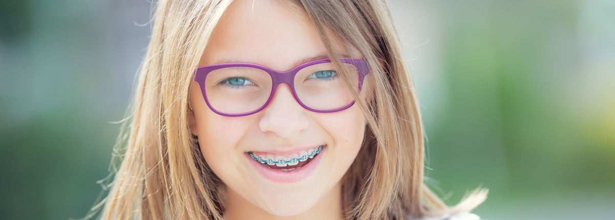 blondes Kind mit lila-farbiger Brille und einer festen Zahnspange mit blauen Gummis
