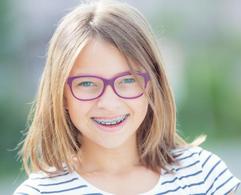 Junges Mädchen lächelt nachdem ihr eine feste Zahnspange im Rahmen der kieferorthopädischen Behandlung eingesetzt wurde