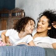 Mutter mit fester Zahnspange und Tochter lächeln sich an