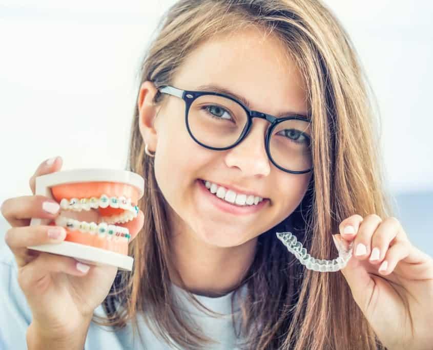 Junges Frau lächelt und hält eine lose sowie eine feste Zahnspange in den Händen