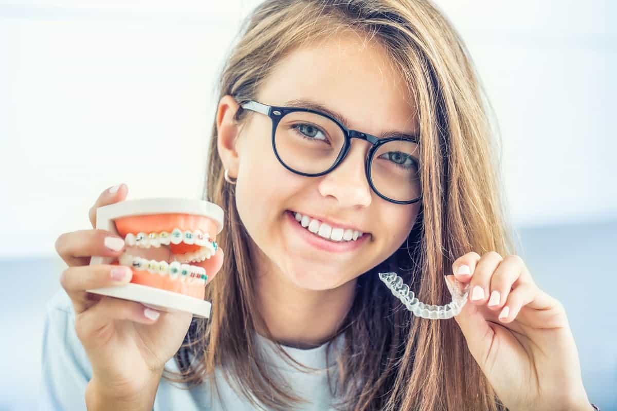 lächelnde Jugendliche mit Zahnspange in der einen und Aligner-Zahnschiene in der anderen Hand